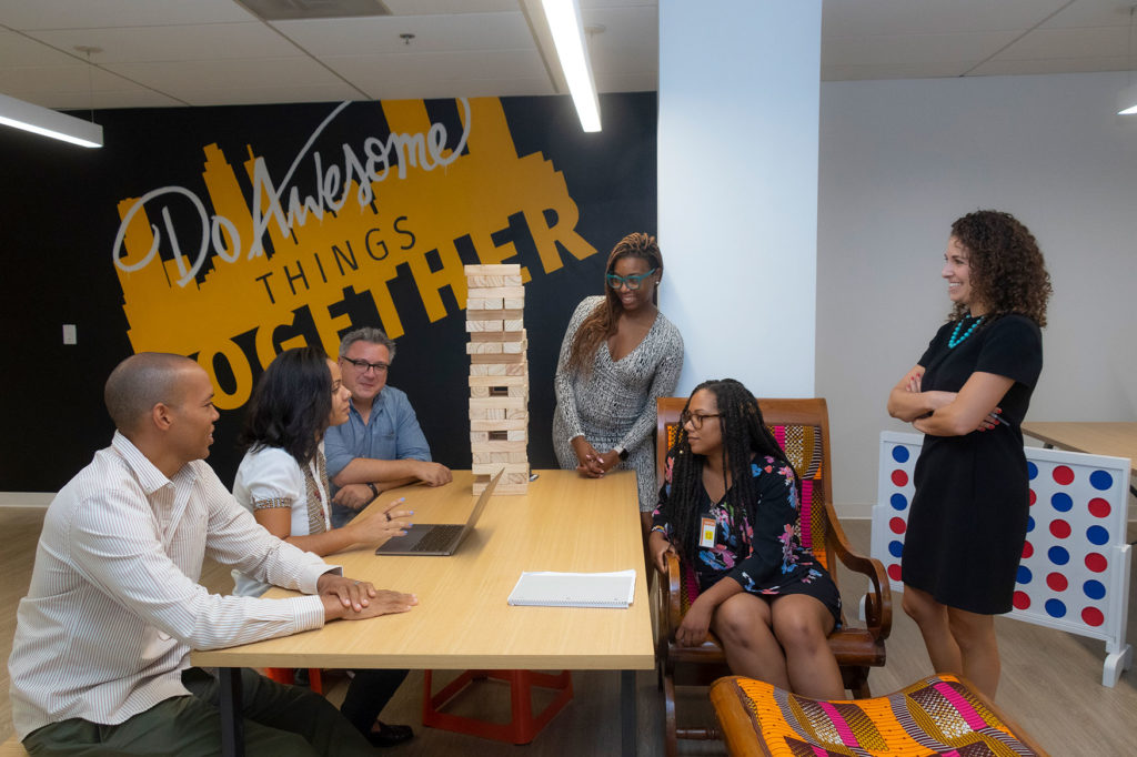 A group of people play Giant Jenga on a table.