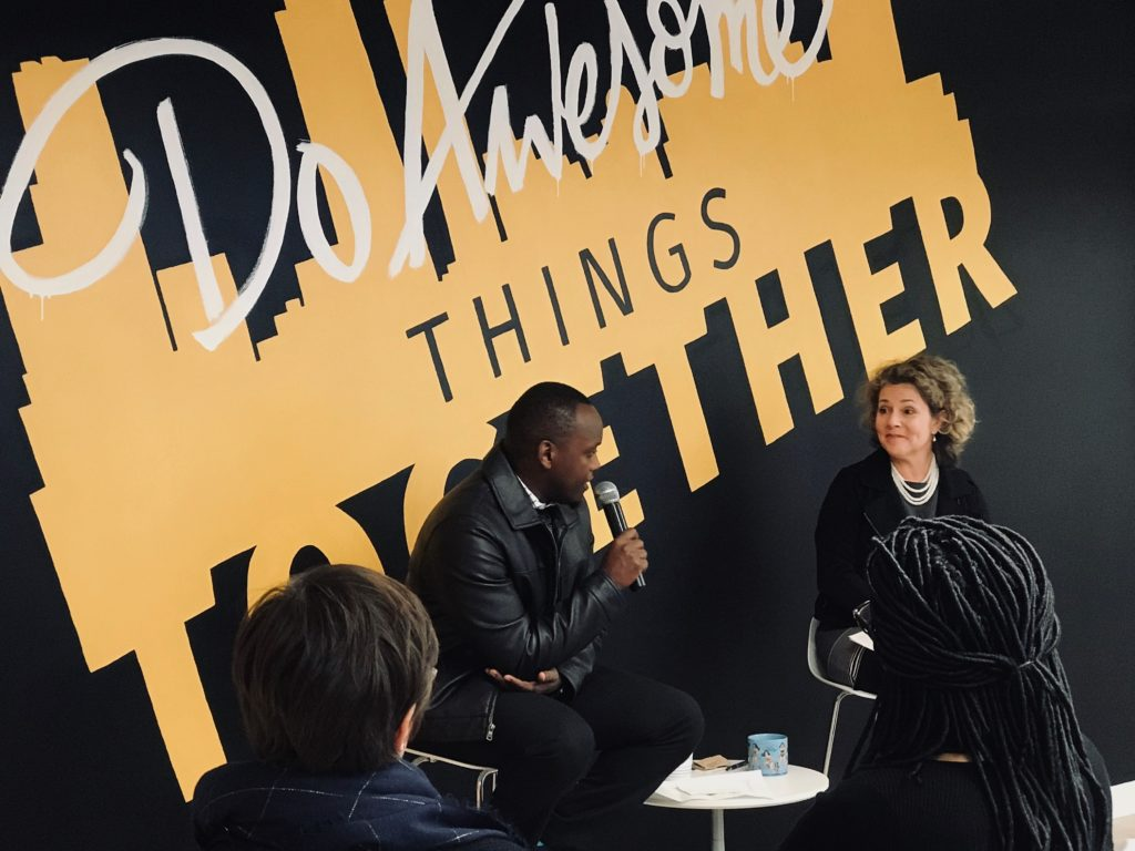 "A man and woman sit in conversation in front of the ""Do Awesome Things Together"" mural in the ATL Innovation Hub."
